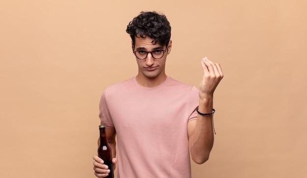 Giovane con una birra che fa capice o un gesto di denaro, dicendoti di pagare i tuoi debiti!