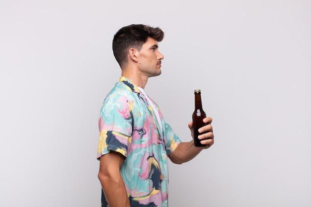 Giovane con una birra sulla vista di profilo che cerca di copiare lo spazio davanti, pensare, immaginare o sognare ad occhi aperti