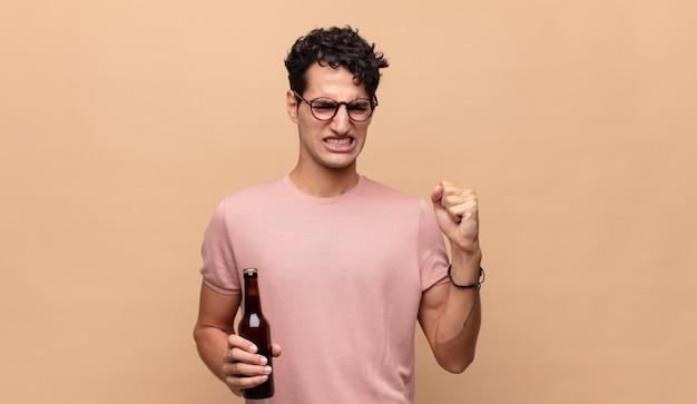Giovane con una birra che grida in modo aggressivo con un'espressione arrabbiata o con i pugni chiusi per celebrare il successo