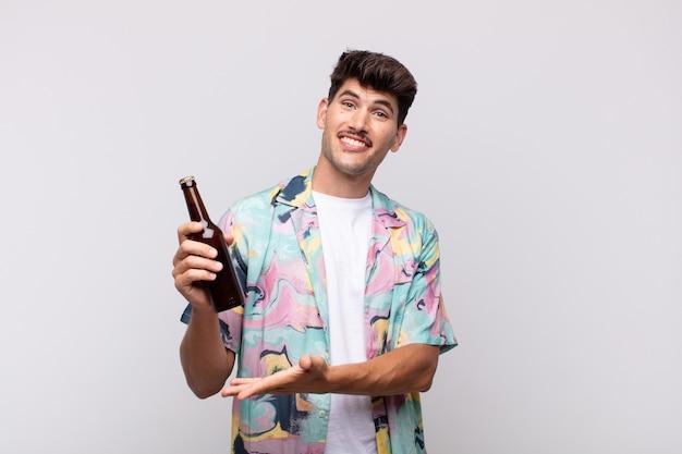 Giovane con una birra che sorride allegramente, sentendosi felice e mostrando un concetto nello spazio della copia con il palmo della mano