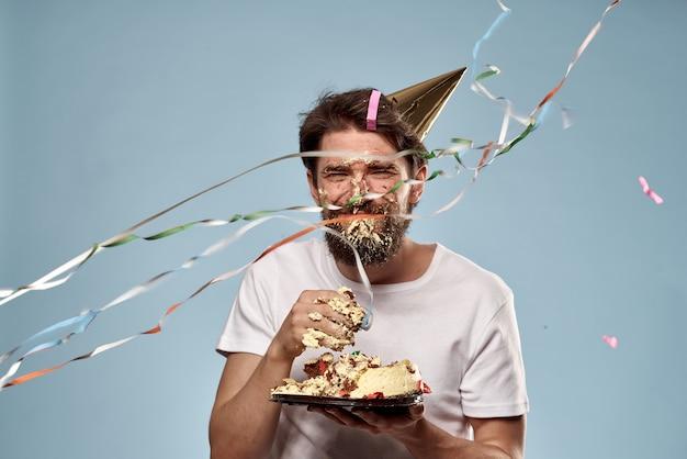 Un giovane con una torta di compleanno è caduto in faccia con una torta, la faccia in una torta