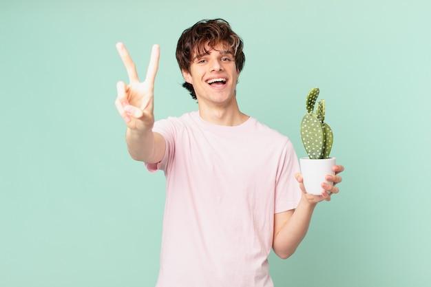 Giovane con un cactus che sorride e sembra felice, gesticolando vittoria o pace