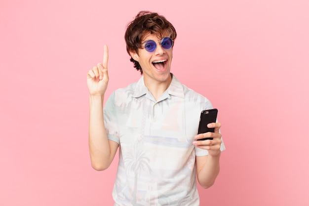 Giovane con un telefono cellulare che si sente come un genio felice ed eccitato dopo aver realizzato un'idea