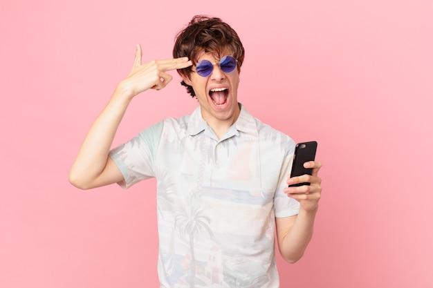 Giovane con un telefono cellulare che sembra gesto di suicidio infelice e stressato che fa il segno della pistola