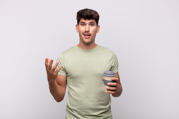 Giovane con un caffè che si sente felice, sorpreso e allegro, sorridente con atteggiamento positivo, realizzando una soluzione o un'idea
