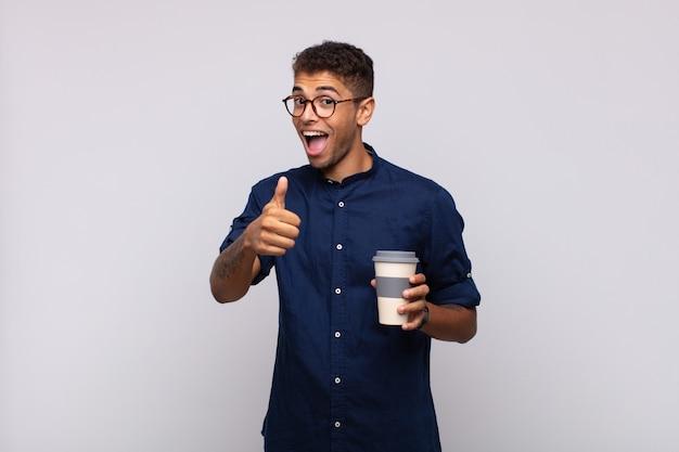 Giovane con un caffè che si sente orgoglioso, spensierato, fiducioso e felice, sorridendo positivamente con i pollici in su