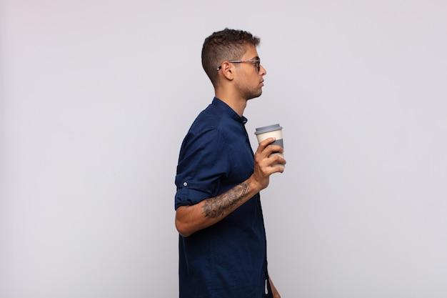 Giovane con un caffè sulla vista di profilo che cerca di copiare lo spazio davanti, pensando, immaginando o sognando ad occhi aperti