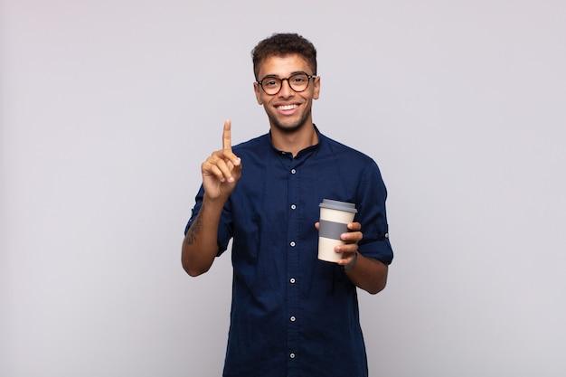 Giovane con un caffè che sorride e sembra amichevole, mostrando il numero uno o il primo con la mano in avanti, il conto alla rovescia