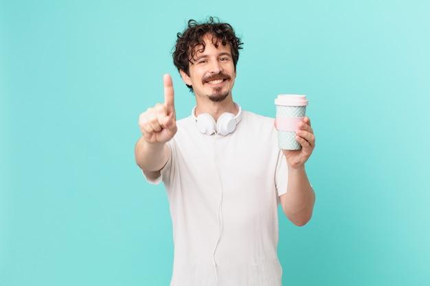 Giovane con un caffè che sorride con orgoglio e sicurezza facendo il numero uno