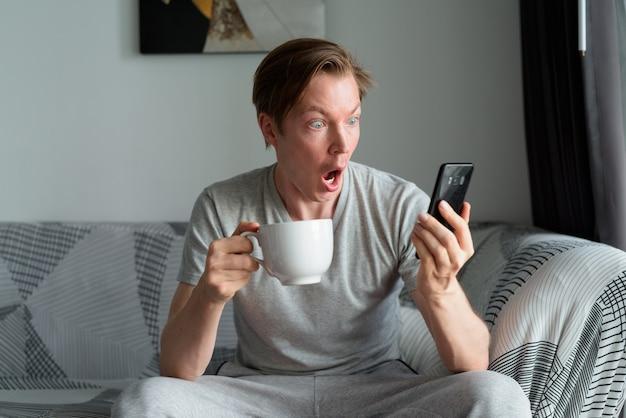 Giovane uomo con caffè utilizzando il telefono e guardando scioccato a casa
