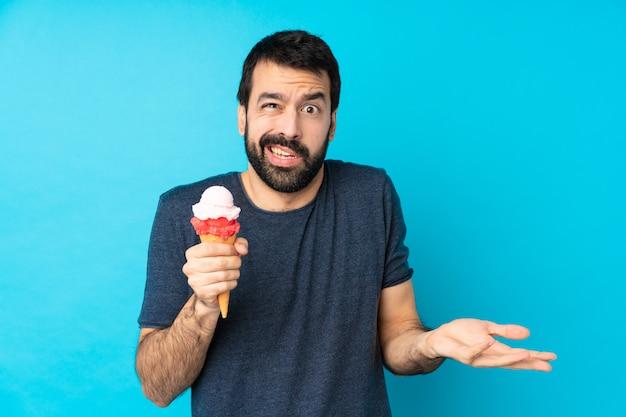 Giovane con un gelato della cornetta sopra la parete blu isolata infelice per non capire qualcosa