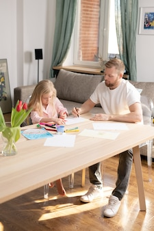 Giovane uomo con il pastello su carta bianca aiutando la sua piccola figlia carina a disegnare un'immagine mentre entrambi seduti da un tavolo di legno nel soggiorno