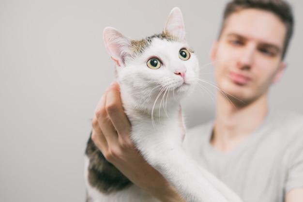 Giovane con simpatico gatto divertente su sfondo chiaro