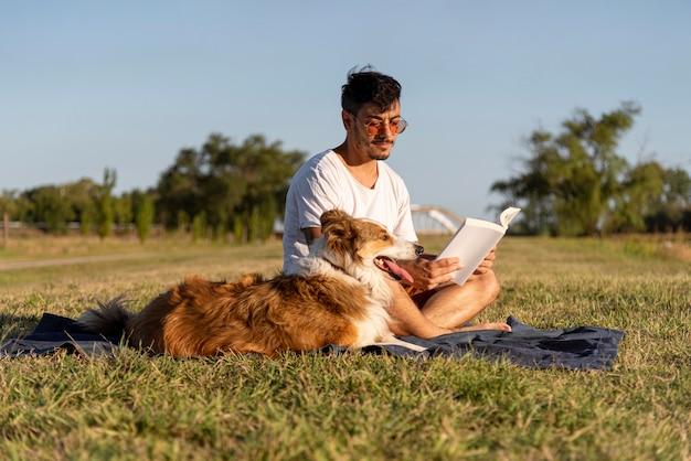 Giovane con il cane in riva al mare a leggere