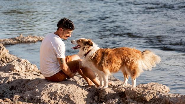 Giovane con cane in riva al mare