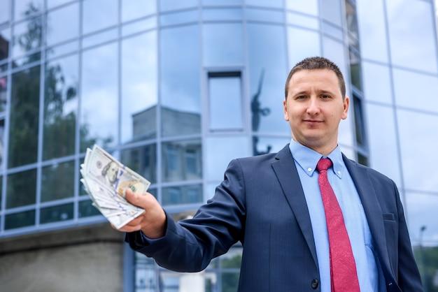 Giovane con banconote in dollari in piedi vicino al centro affari