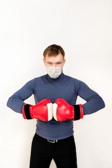 Giovane con espressione minacciosa e determinata in guantoni da boxe rossi su sfondo bianco copia spazio