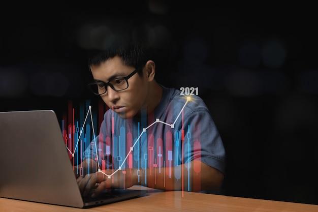 Giovane con occhiali da vista che naviga al suo computer portatile con un grafico in crescita e freccia in alto, concetto di finanza aziendale con un grafico forex.