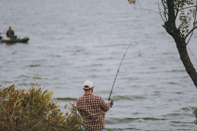 Il giovane con una canna da pesca in camicia a scacchi e berretto lancia un'esca e pesca sullo sfondo di una barca su un lago dalla riva vicino a arbusti e canne. stile di vita, ricreazione, concetto di svago.
