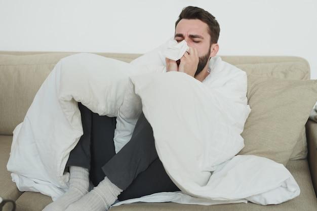 Giovane uomo con influenza o covid19 tossisce nel fazzoletto o fazzoletto di carta mentre è seduto sul divano nel soggiorno durante l'autoisolamento