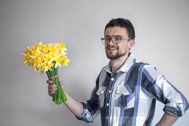Giovane con gli occhiali e un mazzo di fiori.