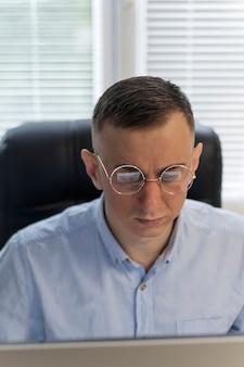 Il giovane con gli occhiali sta lavorando a un progetto. ritratto di un uomo mentre lavora al computer. il giovane sta lavorando al progetto