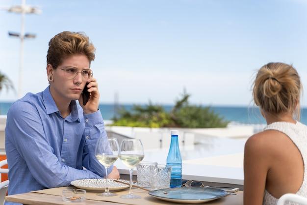 Giovane uomo con gli occhiali e piercing seduto su un tavolo a parlare con un cellulare