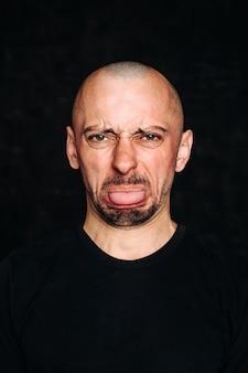 Un giovane con una smorfia di disgusto sul viso. tira fuori la lingua. il concetto di emozioni negative. ritratto isolato su sfondo nero. l'emozione è disprezzo, disgusto.