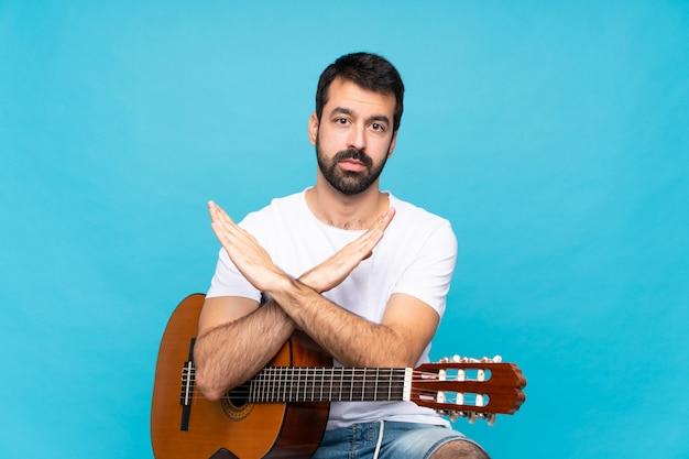 Giovane con la chitarra sopra il blu isolato che non fa gesto