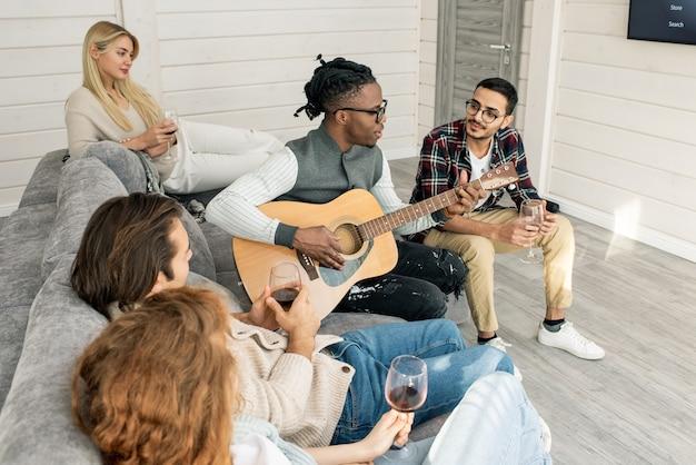 Giovane con la chitarra che canta per i suoi amici seduti intorno a lui sul divano e bevendo vino a casa festa in soggiorno