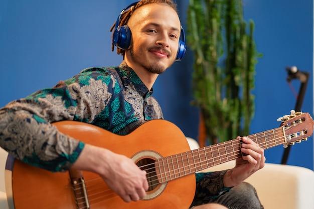 Giovane uomo con le cuffie seduto sul divano e suonare la chitarra