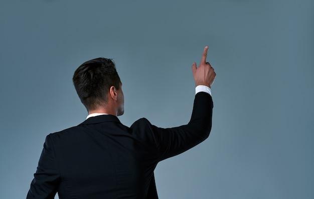 Un giovane di spalle si è girato verso la telecamera, indicando qualcosa. esecutivo dell'uomo d'affari che indica in su.