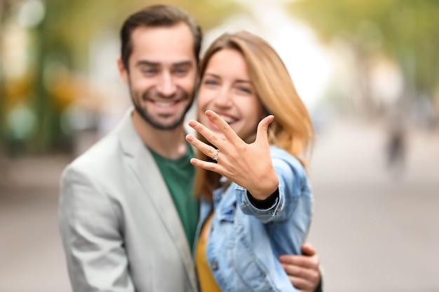 Giovane con la sua amata mostra anello di fidanzamento all'aperto