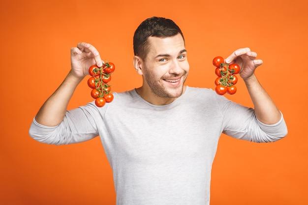 Giovane uomo con tiene bacche di pomodoro isolato su sfondo arancione