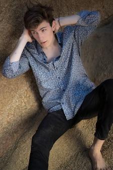 Giovane con jeans e camicia bianca tra le rocce