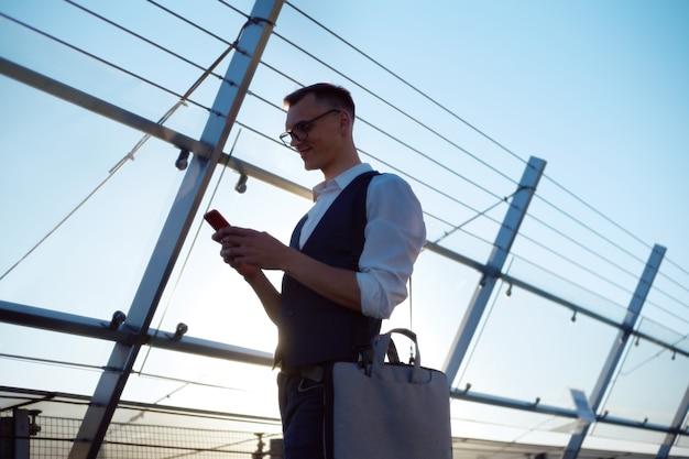 Giovane con una borsa per laptop che legge un messaggio sul suo smartphone