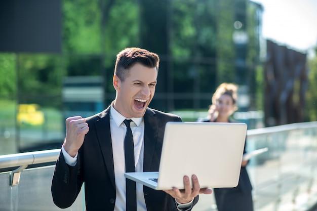 Giovane con un computer portatile che si rallegra entusiasticamente