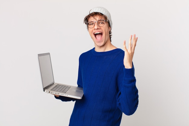 Giovane con un laptop che si sente felice e stupito per qualcosa di incredibile
