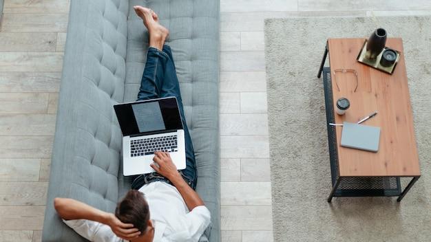 Giovane con un computer portatile sdraiato sul divano