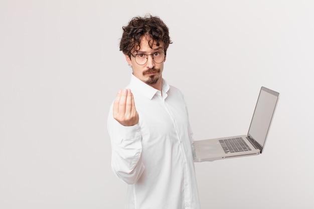 Giovane con un laptop che fa un gesto capice o denaro, dicendoti di pagare