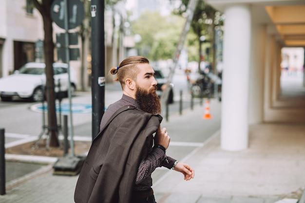Giovane uomo con la barba lunga sulla strada della città.