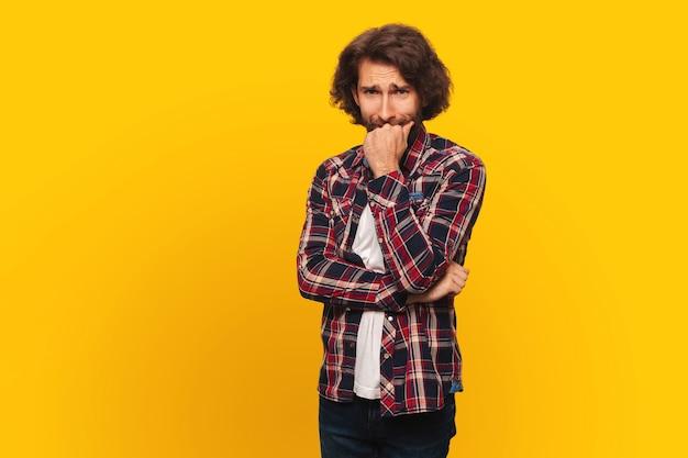 Un giovane con lunghi capelli ricci e barba è preoccupato, si morde il pugno, sfondo giallo