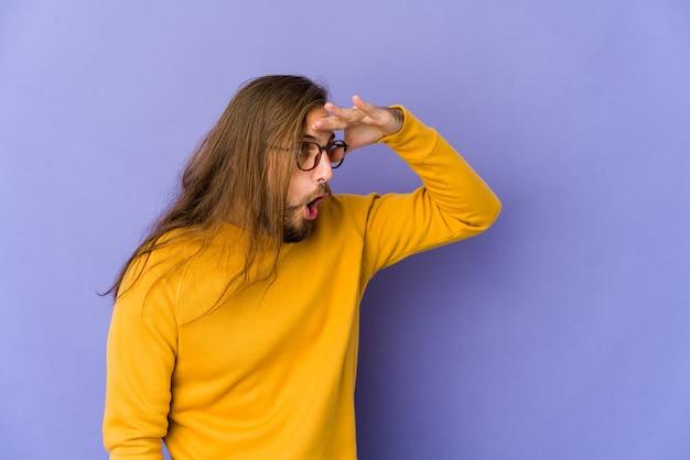 Giovane uomo con i capelli lunghi guarda lontano tenendo la mano sulla fronte.