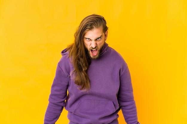 Giovane uomo con i capelli lunghi guarda gridando molto arrabbiato, concetto di rabbia, frustrato.