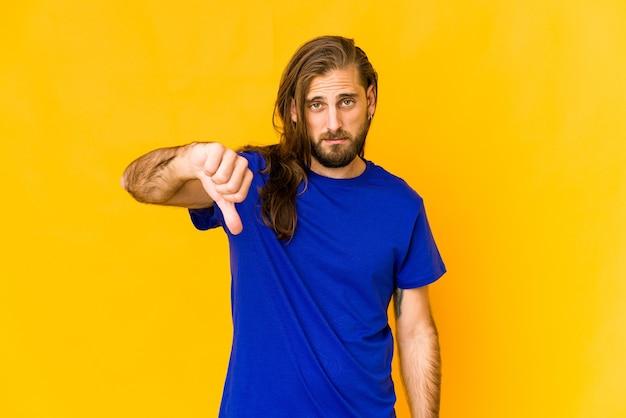 Il giovane con i capelli lunghi guarda che mostra un gesto di antipatia, i pollici in giù. concetto di disaccordo.