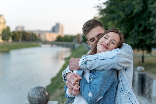 Il giovane con amore abbraccia la sua amata sullo sfondo del paesaggio urbano. dolce abbraccio sullo sfondo della città. appuntamento romantico.