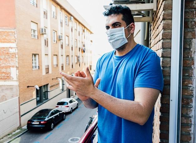 Giovane con maschera che applaude dalla terrazza al tramonto le persone che stanno combattendo contro il coronavirus