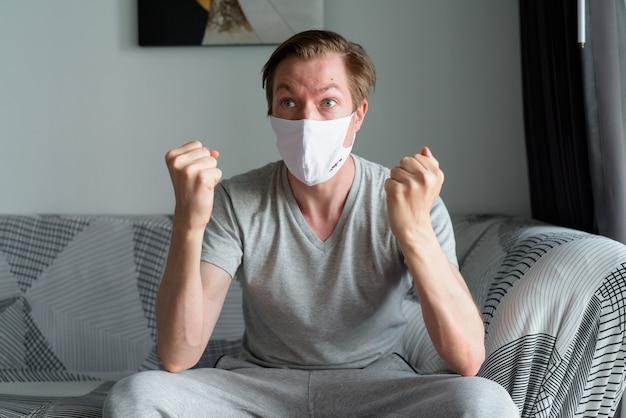 Giovane uomo con maschera che ottiene buone notizie a casa in quarantena