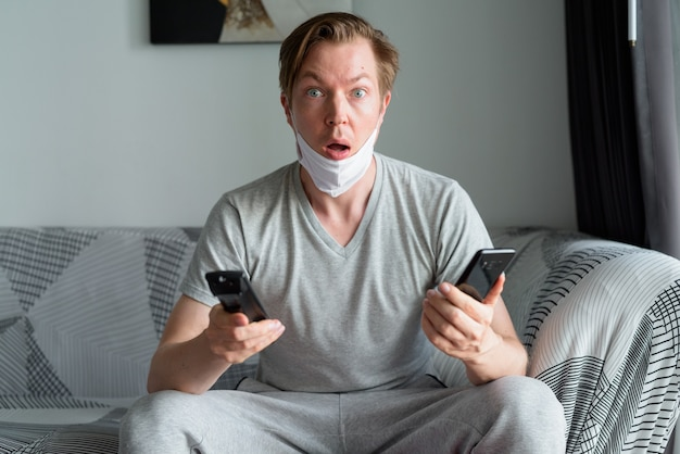 Giovane con la maschera che tiene il telefono mentre si guarda la tv e sembra scioccato a casa in quarantena
