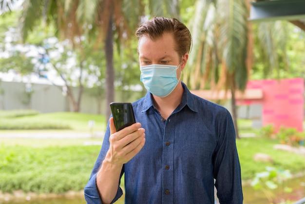 Giovane con maschera per la protezione dall'epidemia di coronavirus utilizzando il telefono al parco